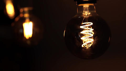 Tungsten light bulb lamps over black background. Concept of light and dark, idea Footage