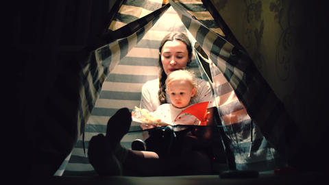 Mom and her little baby read a book together in a teepee in the evening Footage