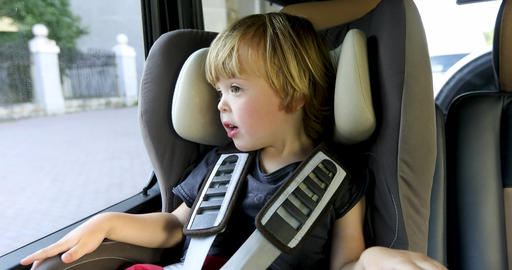 Adorable kid sitting in car seat in car Live Action