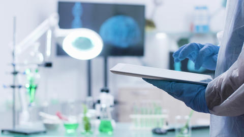Chemist typing on a digital tablet PC while wearing gloves Live Action