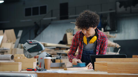 Girl busy polishing wood with abrasive block in workplace in timber workshop Live Action