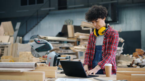 Female worker using laptop in wood workshop typing standing in workplace alone Live Action