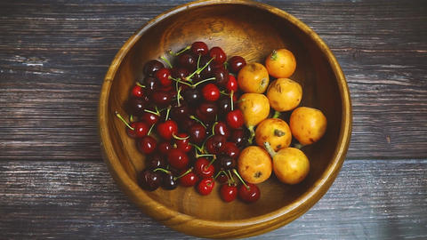 Japanese plum or Japanese medlar and cherries in wooden bowl rotating. Fresh fruits. Vegetarian Footage