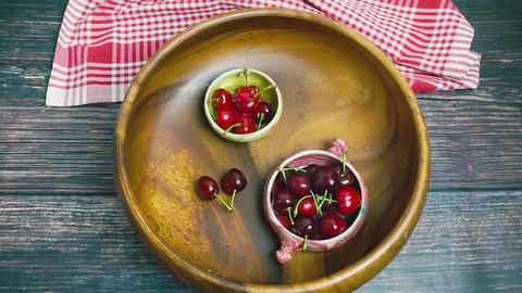 Fresh red cherries in bowl rotating. Wooden background. Red summer fruits Footage