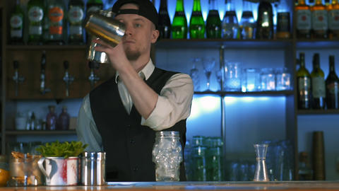 The bartender begins to prepare an alcoholic cocktail Live Action