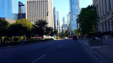 Viewpoint of Downtown City People and Traffic Along Street Surrounded by Tall Buildings in Summer Footage