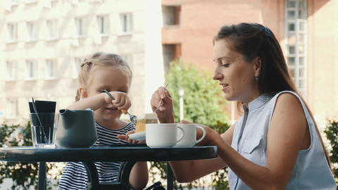 Beautiful Caucasian Mother And Little Daughter Eat Cake Together In Outdoor Cafe Live Action