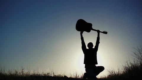 Male Figure Lifting Guitar Overhead Stock Video Footage