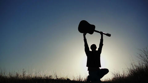 Male Figure Lifting Guitar Overhead Footage