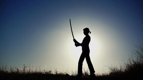 Silhouette of Girl Practicing With Sword Footage