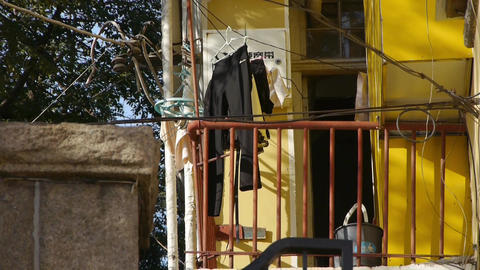 Tree with old house,dry clothes at balcony & lush... Stock Video Footage