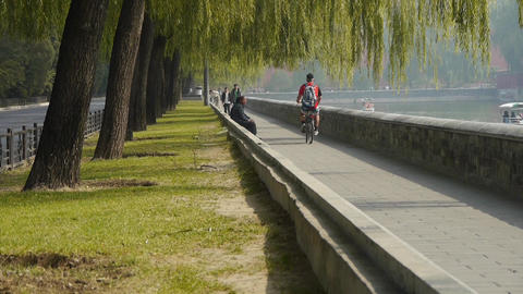 A man riding bicycle relying on willow river.yacht on lake,Road of Forbidden Cit Footage