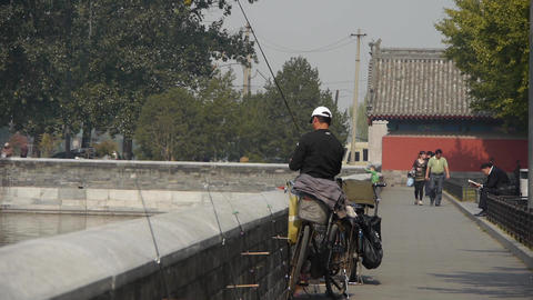 Fisherman fishing by sparkling moat lake relying on fence in Beijing Forbidden C Footage