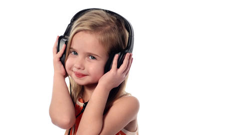 little girl listening to music on headphones Footage