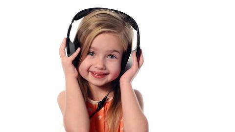 little girl listening to music on headphones Stock Video Footage
