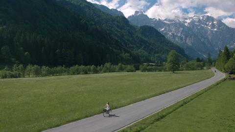 Aerial - Distant shot of young woman riding bicycle on scenic rural road Footage