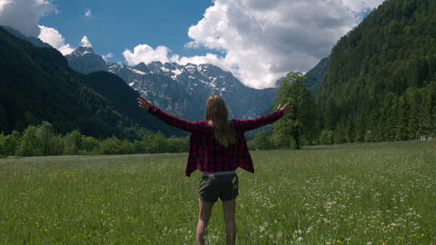 Jib shot behind a woman standing in the meadow and raising arms Live Action