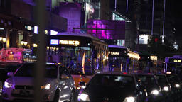 bus and car traffic in busy street in macau at night Footage