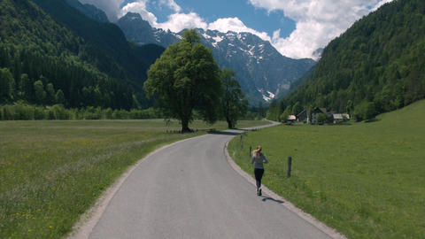 Aerial - Flyover young woman jogging on scenic rural road, back view Footage
