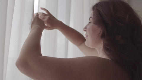 Cute mature woman opening curtain lace standing in luxury apartment home or Footage