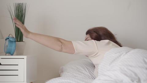 Adult sleepy woman turning off the alarm clock. Blue old-fashioned alarm clock Footage