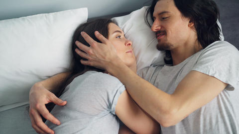 Girl and guy hugging talking rubbing noses in bed in cosy apartment Live Action