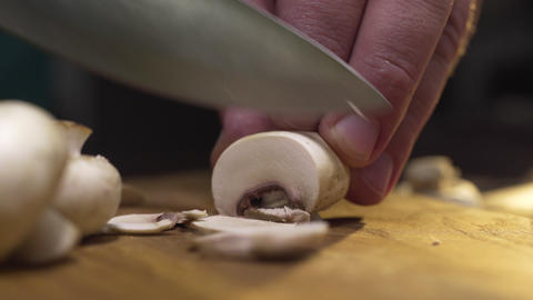 Macro video of the cook slices raw champignons on the wooden board, cooking the Live Action