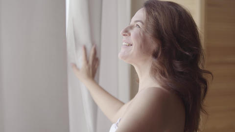Pretty mature woman opening curtain lace standing in luxury apartment home or Footage