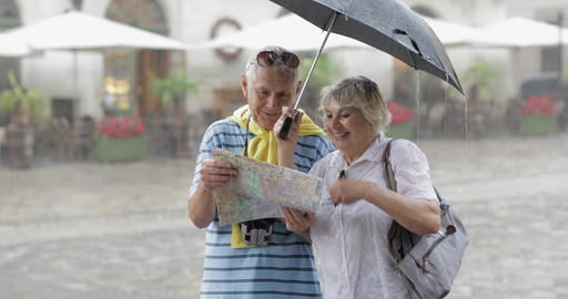 Senior tourists in rainy weather stand and looking for the route in map Live Action