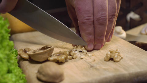 Close up video: chef cuts walnuts on the wooden board, cooking salad, vitamin Footage
