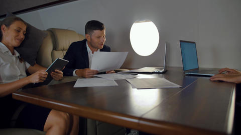 Rich business people discussing about business inside of private jet cabin Live Action