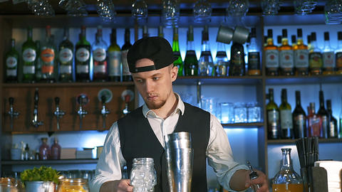 Guy-bartender starts his master class of preparation an alcohol cocktail Live Action