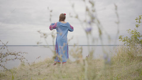 Rear view at carefree caucasian woman wearing long summer fashion dress standing Live Action