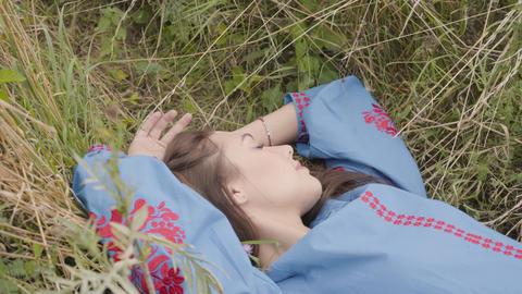 Cute carefree caucasian girl wearing long summer fashion dress lying on the Footage