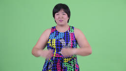 Happy young overweight Asian woman with hand heart gesture ready to party Footage