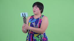 Happy young overweight Asian woman vlogging and showing phone ready to party Footage