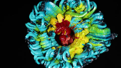 Slowly revolving colorful flower made by pigments Footage
