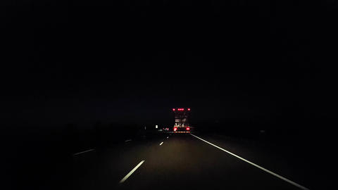 Drafting Large Truck on Highway During Night. Driver Point of View POV Slipstreaming by Following Live Action