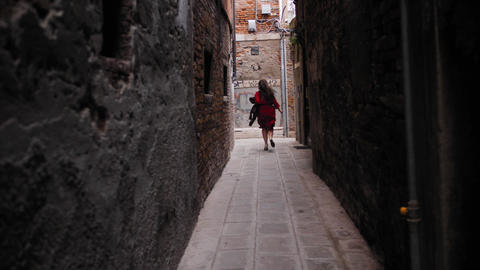 Carefree female tourist with hat in hand running in the of venice yard Live Action