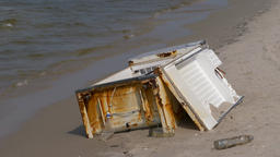 Environment pollution. Old, rusty fridge on the beach Live Action