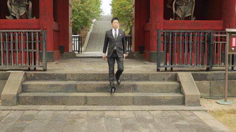 Japanese businessman walking through a japanese gate Live Action