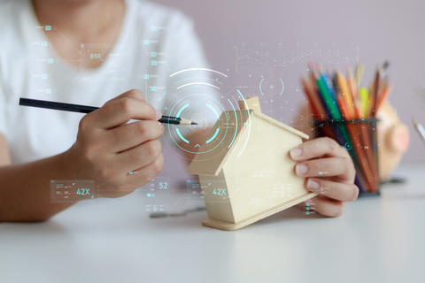 Happy Asian woman using pencil to draw with wooden house piggy b フォト