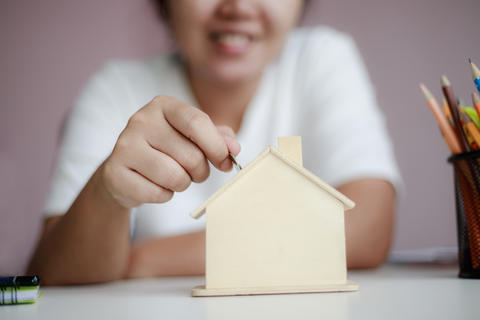 Happy Asian woman putting coin to house piggy bank 002 フォト