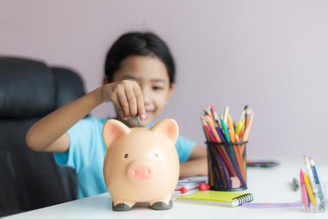 Little asian girl putting money coin into piggy bank 010 フォト