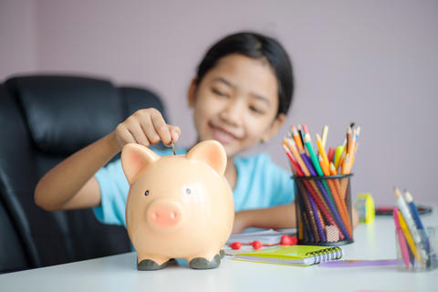 Happy little asian girl putting money coin into piggy bank selec フォト