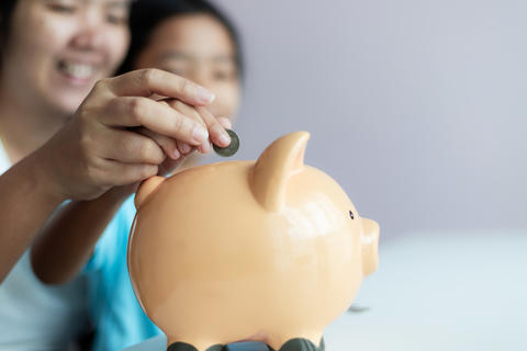 Mother and daughter putting coin into the piggy bank 001 フォト