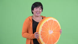 Happy young overweight Asian woman with orange pillow as healthy concept ready Footage