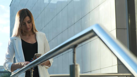 Beautiful business lady is reading a message in a smartphone Live Action