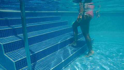 Woman in a bikini walking underwater swimming pool steps Live Action
