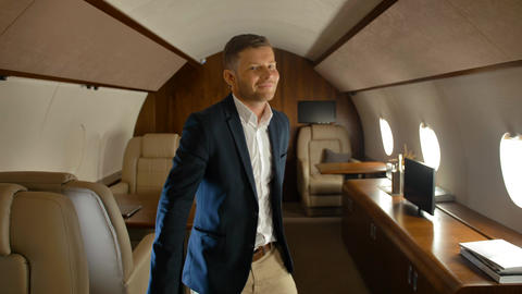 Cheerful confident businessman dancing inside of luxury jet Footage